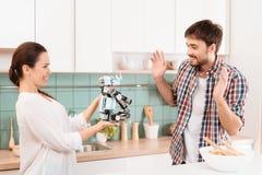 Un jeune type faisait une salade dans la cuisine La fille lui a donné un robot de rhinocéros Le type est captivé Images stock