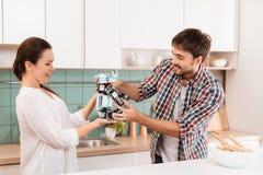 Un jeune type faisait une salade dans la cuisine La fille lui a donné un robot de rhinocéros Le type est captivé Photo stock