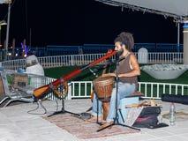 Un jeune type joue un darbuka et un grand tuyau le soir sur le bord de mer dans la ville de Nahariya, en Israël Photo stock