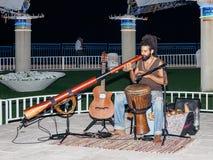 Un jeune type joue un grand tuyau le soir sur le bord de mer dans la ville de Nahariya, en Israël Photographie stock
