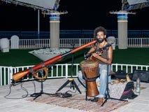 Un jeune type joue une guitare le soir sur le bord de mer dans la ville de Nahariya, en Israël Photographie stock