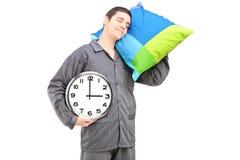 Un jeune type paresseux retenant une horloge murale et dormant sur un oreiller Images libres de droits