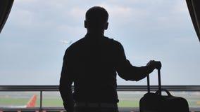 Un jeune type regarde l'avion décollant de la fenêtre de sa chambre d'hôtel et des feuilles avec une valise pour l'embarquement banque de vidéos