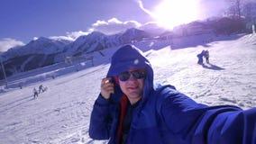 Un jeune type regarde la caméra, met dessus une lance sur sa tête Apprécie les montagnes couronnées de neige d'hiver Utiliser un  banque de vidéos