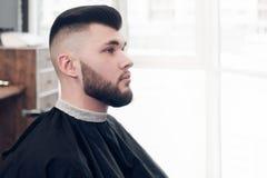 Un jeune type s'asseyant sur une chaise dans le raseur-coiffeur Image stock