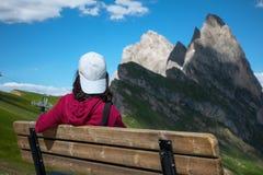 Un jeune voyageur sur le banc avec le fond de la crête de Seceda images stock