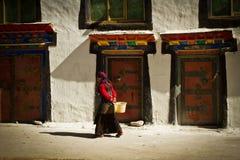 Un jeune woma marche dans un village tibétain du sud à distance Photo stock