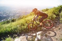 Un jinete en un casco está montando a lo largo de una trayectoria de la grava de una cuesta de montaña en una bici de montaña Imagenes de archivo