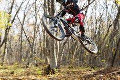 Un jinete joven en la rueda de su bici de montaña hace un truco en el salto en el trampolín de la montaña en declive Fotos de archivo