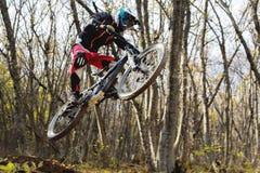 Un jinete joven en la rueda de su bici de montaña hace un truco en el salto en el trampolín de la montaña en declive Imagen de archivo libre de regalías