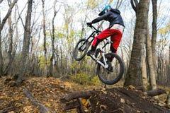 Un jinete joven en la rueda de su bici de montaña hace un truco en el salto en el trampolín de la montaña en declive Imágenes de archivo libres de regalías