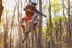 Un jinete joven en la rueda de su bici de montaña hace un truco en el salto en el trampolín de la montaña en declive Imagen de archivo
