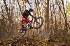 Un jinete joven en la rueda de su bici de montaña hace un truco en el salto en el trampolín de la montaña en declive Foto de archivo libre de regalías