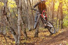 Un jinete joven en la rueda de su bici de montaña hace un truco en el salto en el trampolín de la montaña en declive Imagenes de archivo