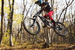 Un jinete joven en la rueda de su bici de montaña hace un truco en el salto en el trampolín de la montaña en declive Fotografía de archivo libre de regalías