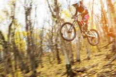 Un jinete joven en la rueda de su bici de montaña hace un truco en el salto en el trampolín de la montaña en declive Fotografía de archivo