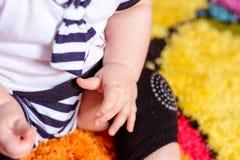 Un joli bébé dans une chemise rayée et des chapeaux posés sur le tapis dans la chambre photo stock