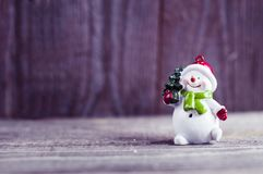 Un jouet de bonhomme de neige porte un arbre de Noël au-dessus de fond en bois Images libres de droits