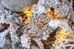 Un jouet sous forme de flocon de neige sur un arbre de Noël décoré Photographie stock