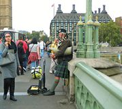 Un joueur écossais de cornemuse sur un pont occupé de Westminster à Londres photos stock