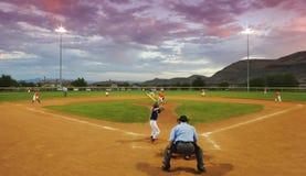 Un joueur manie la batte dans un jeu de baseball crépusculaire Photographie stock libre de droits