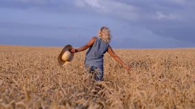 Un jour ensoleillé, une femme marche le long d'un champ de blé avec une robe blanche, dans un chapeau de paille sur un concept de banque de vidéos