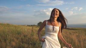 Un jour ensoleillé, une femme marche le long d'un champ de blé avec une robe blanche sur un fond de nature clips vidéos