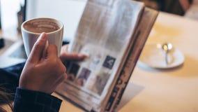 Un journal de lecture de femme d'affaires et un café potable images stock