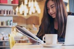 Un journal de lecture de femme d'affaires et un café potable pendant le matin photo stock