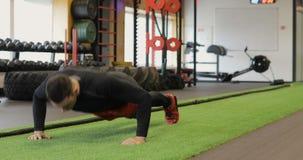 Un joven del ajuste flexiones de brazos que hacen en un pequeño gimnasio, deportista que ejercita en el gimnasio Hombre joven mus almacen de video
