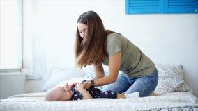Un joven mima a juegos con su hija, besos de una mujer y cosquillas un pequeño bebé almacen de video