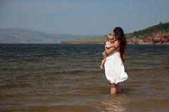 Un joven mima a los controles un niño en sus brazos que se colocan en el mar fotografía de archivo libre de regalías