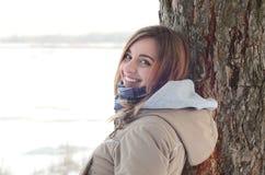 Un joven y una muchacha caucásica sonriente mira alrededor de la línea del horizonte entre el cielo y el lago congelado en invier foto de archivo libre de regalías