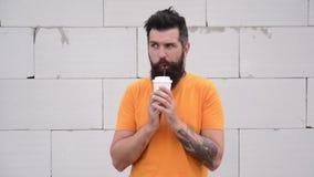Un joyeux mec branché avec du café pour aller s'amuser dehors. Un homme aux oreilles boit du café à l'extérieur clips vidéos