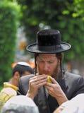 Un judío ortodoxo en sidelocks largos escoge la fruta cítrica Fotos de archivo libres de regalías