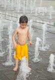 Un juego asiático del muchacho por la fuente de agua Imagen de archivo libre de regalías