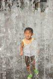 Un juego asiático del muchacho por la fuente de agua Fotos de archivo libres de regalías