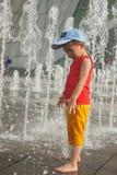 Un juego asiático del muchacho por la fuente de agua Foto de archivo libre de regalías