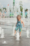 Un juego asiático del muchacho por la fuente de agua Fotografía de archivo