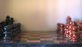Un juego de ajedrez de piedra con los pedazos rojos y negros, alista para comenzar Imagenes de archivo