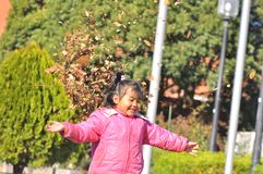 Un juego de la muchacha con las hojas secas Imagenes de archivo