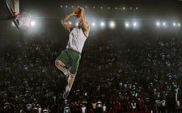 Un jugador de básquet salta en la opinión del panorama del estadio Imagen de archivo