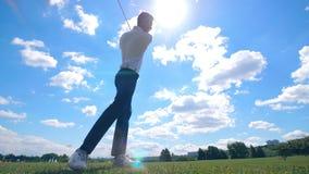 Un jugador de golf golpea una bola en un campo Jugador de golf en un campo de golf almacen de metraje de vídeo