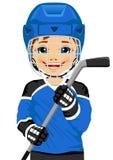 Un jugador de hockey joven en uniforme con un palillo del hockey sobre hielo Foto de archivo libre de regalías