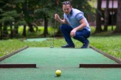 Un jugador del mini-golf mira el resultado de un soplo al lado del bolsillo imagen de archivo libre de regalías