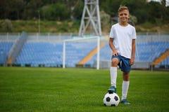 Un jugador deportivo con una bola del fútbol bajo su pie en una hierba verde en un fondo del estadio Afición, concepto de las act Fotografía de archivo libre de regalías