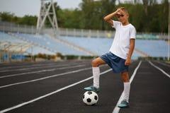 Un jugador deportivo con una bola del fútbol bajo su pie en una hierba verde en un fondo del estadio Afición, concepto de las act Imagenes de archivo