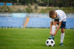 Un jugador deportivo con una bola del fútbol bajo su pie en una hierba verde en un fondo del estadio Afición, concepto de las act Imágenes de archivo libres de regalías