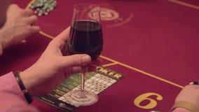 Un jugador en un casino con un vidrio de vino hace apuestas En las manos del marco solamente almacen de metraje de vídeo