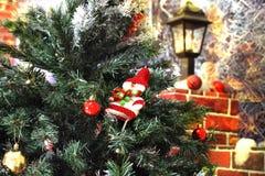 Un juguete de un muñeco de nieve y las bolas cuelgan en un árbol que se coloca cerca de una cerca con una linterna Fotografía de archivo